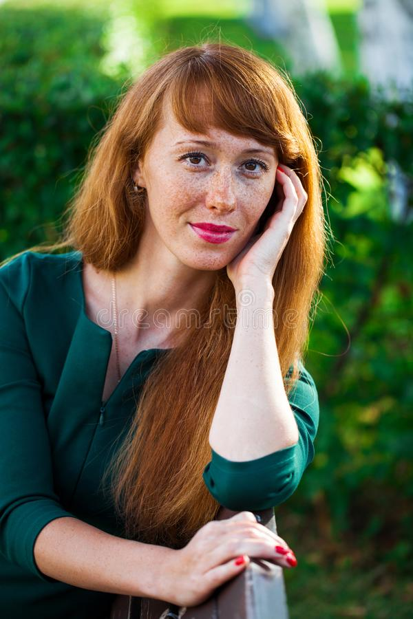 Beautiful young red hair woman posing on summer park. Close up portrait beautiful young red hair woman posing on summer park royalty free stock photography