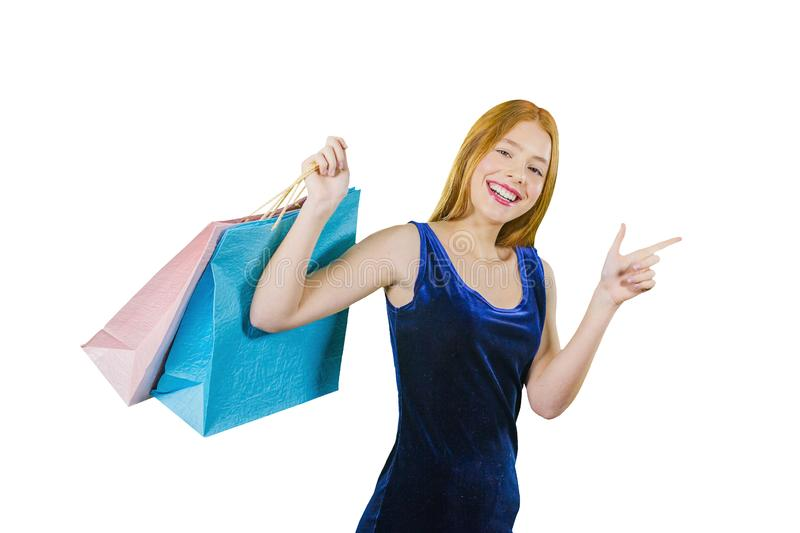 A beautiful young red-haired girl in a blue velvet dress holds gift purchases in one hand, and shows off to the side stock photo