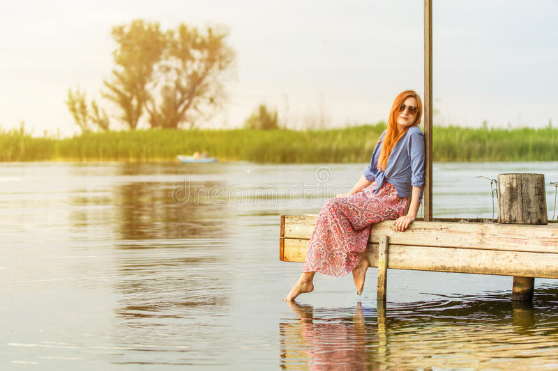 Beautiful young red haired girl in colorful long sarafan dress sitting on a wooden pier on a river or lake. Green bulrush and tree stock photography