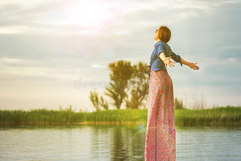 Beautiful young red haired girl in colorful long sarafan dress sitting on a wooden pier on a river or lake. Green bulrush and tree stock image