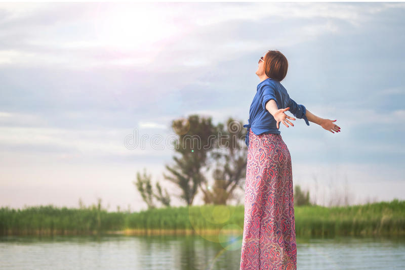 Beautiful young red haired girl in colorful long sarafan dress stands on a stump on a wooden pier on a river or lake. Green bulrus stock photos