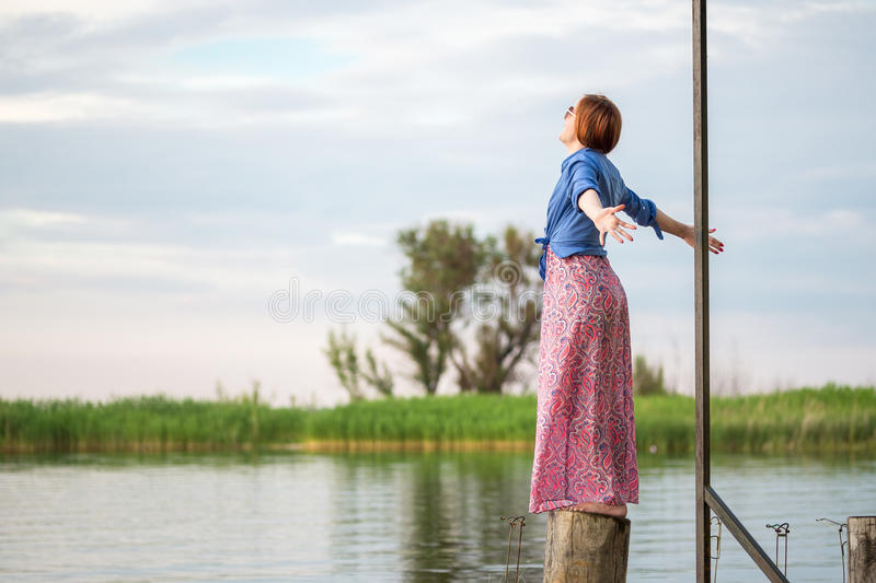Beautiful young red haired girl in colorful long sarafan dress stands on a stump on a wooden pier on a river or lake. Green bulrus royalty free stock photo