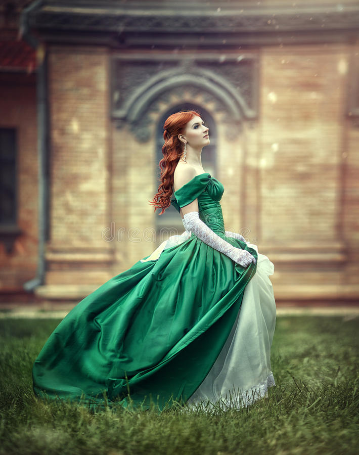 Beautiful, young, red-haired girl in a green medieval dress, climbs the stairs to the castle. stock photo