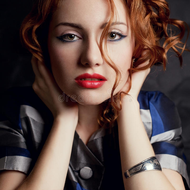 Beautiful young red-haired model in arty jacket. Beautiful young red-haired model in an arty jacket with silver wristband holding her head over black background stock photos