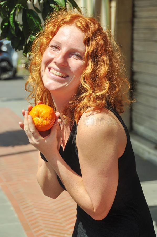Beautiful young red-haired woman, happily keeps a self-picked orange in hands in Liguria Italy in spring on vacation stock photo