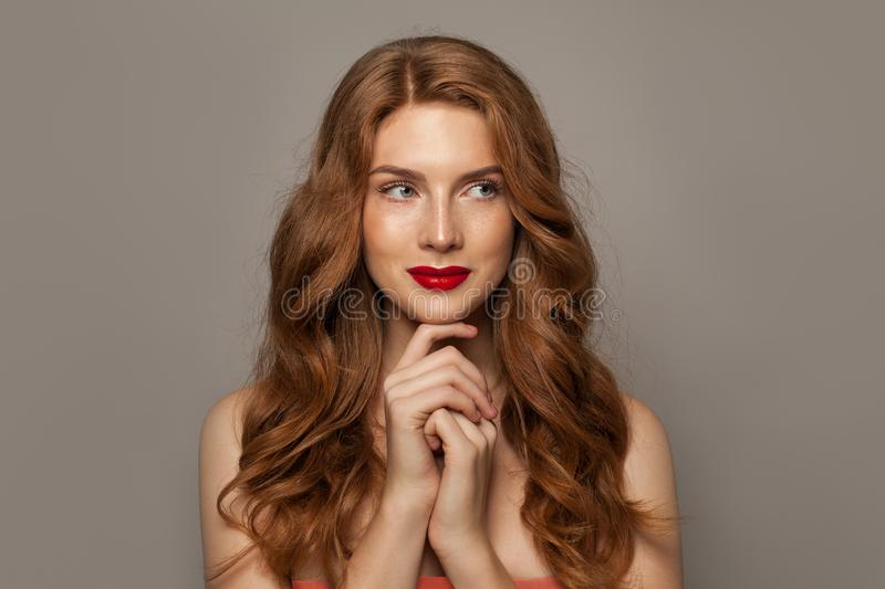 Beautiful young red-haired woman with long beauty curly hair on brown background royalty free stock photo