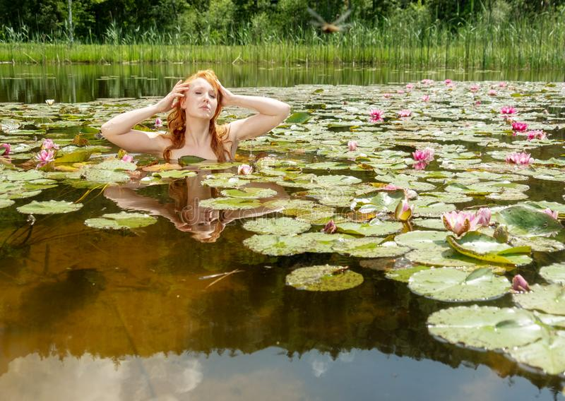 Beautiful young red-haired woman mermaid sensually seductively straightens herself in the water and strokes her hair royalty free stock photo