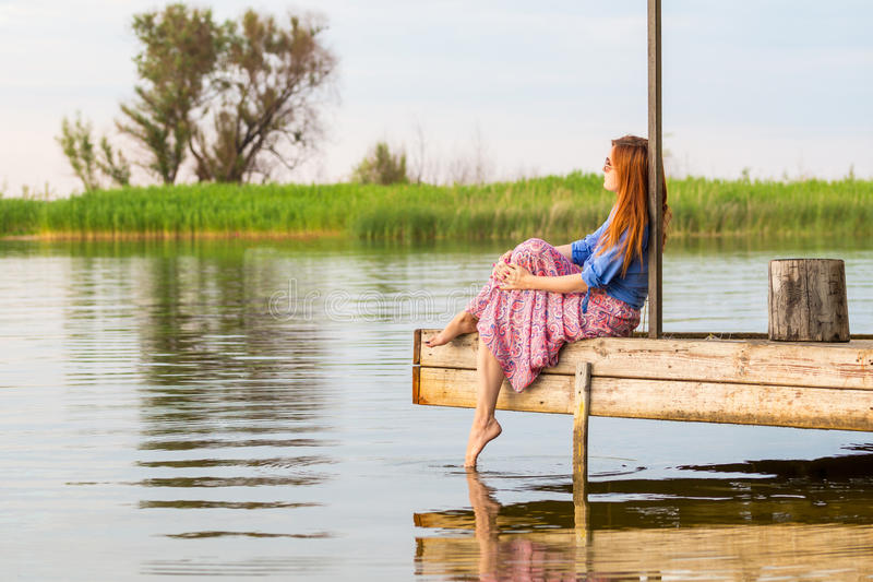 Beautiful young red woman sitting on a wooden pier in a colorful long sarafan dress and putting her leg in a water stock photo