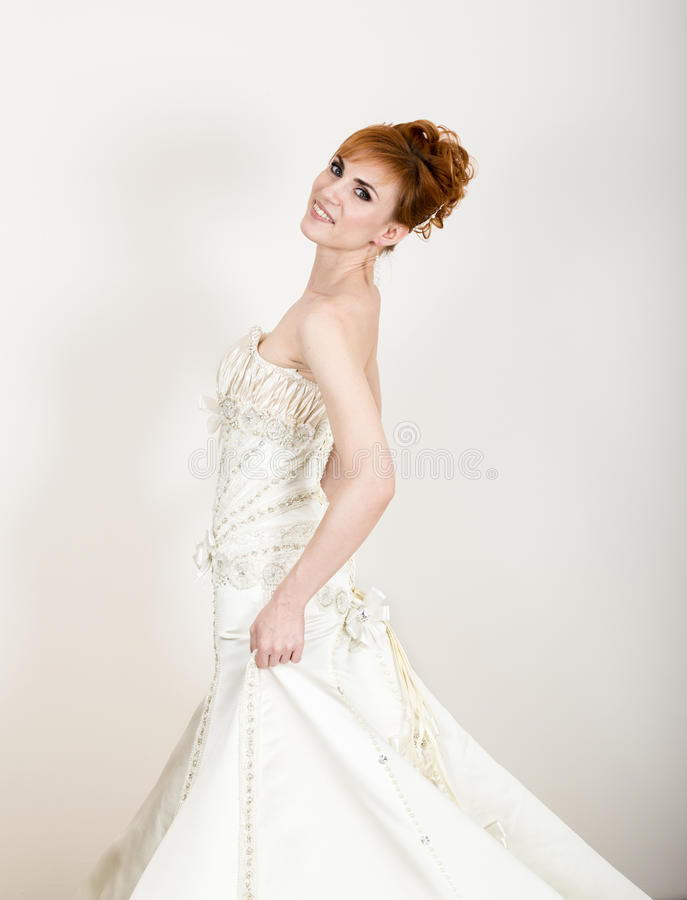 Beautiful young redhead bride wearing white wedding dress with download beautiful young redhead bride wearing white wedding dress with professional make up and hairstyle junglespirit Image collections