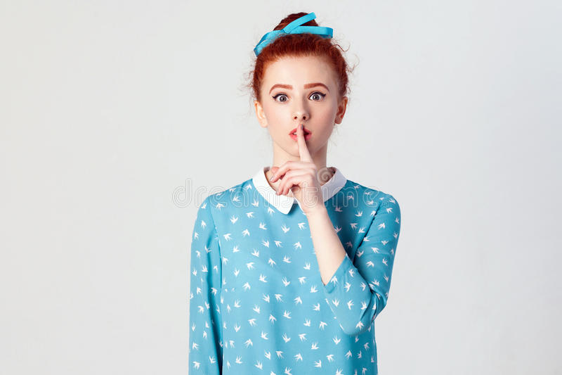 The beautiful young redhead girl, holding index finger at lips, raising brows, saying `Shh`, `Hush`, `Tsss`. stock images
