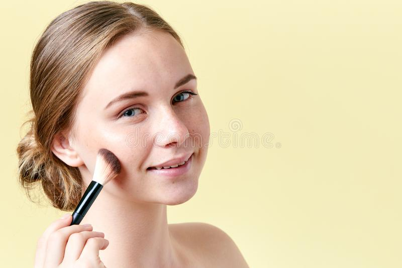 Beautiful young redhead woman with freckles contouring her cheekbones with make up brush. Beauty portrait stock photos