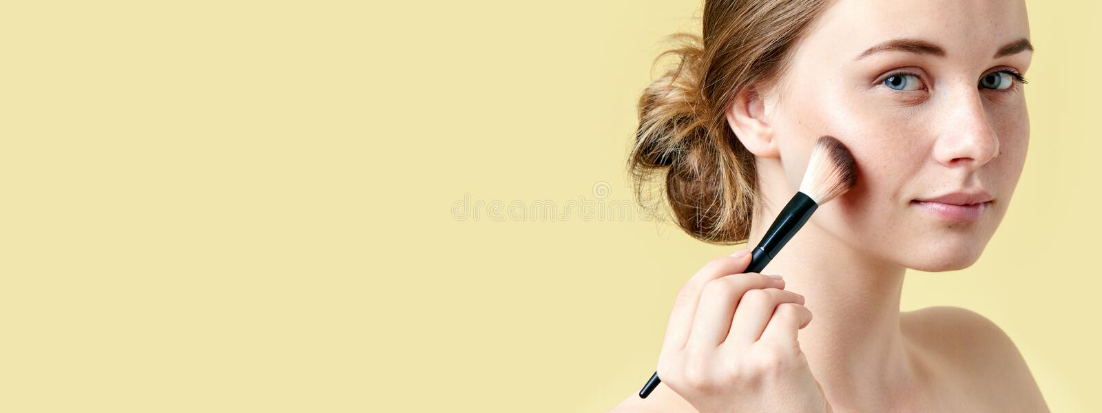 Beautiful young redhead woman with freckles contouring her cheekbones using make up brush. Beauty portrait royalty free stock photo