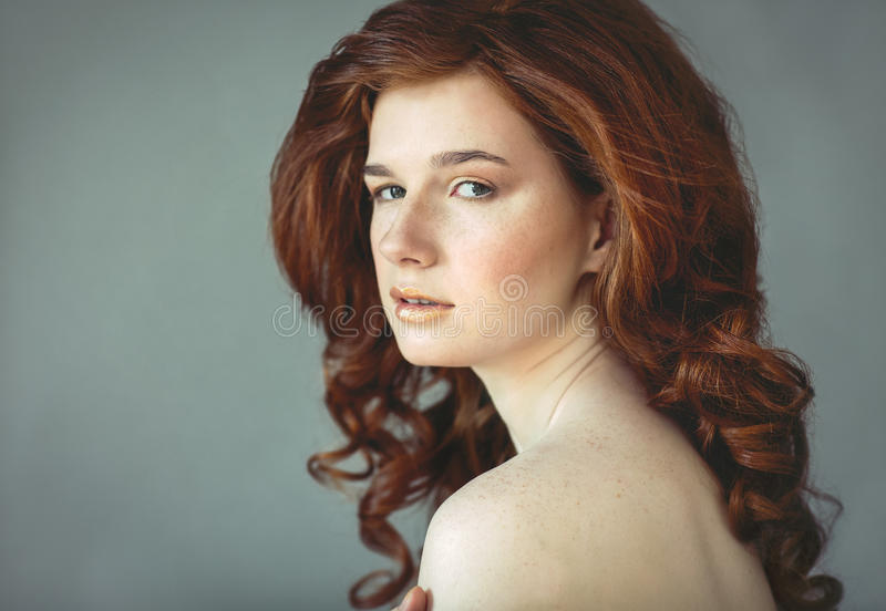 Beautiful young redhead woman with freckles portrait stock image