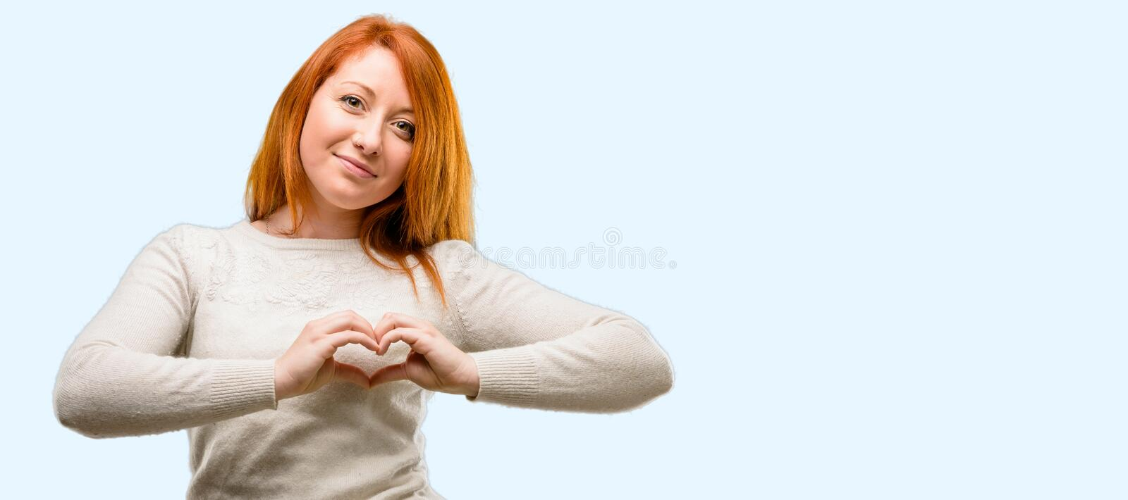 Young beautiful redhead woman isolated over blue background stock images