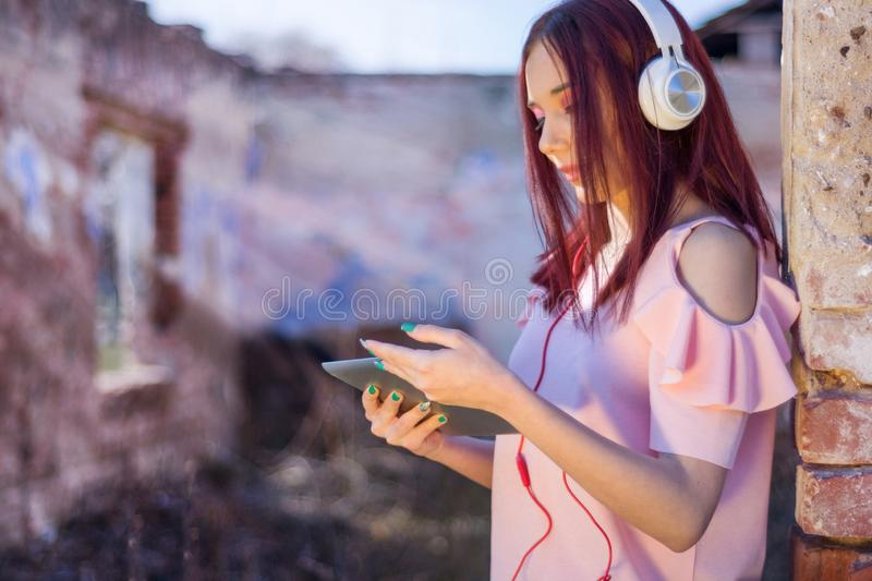 Redheads girl with headphones in the ruins of the house listening to music on digital tablet royalty free stock photos