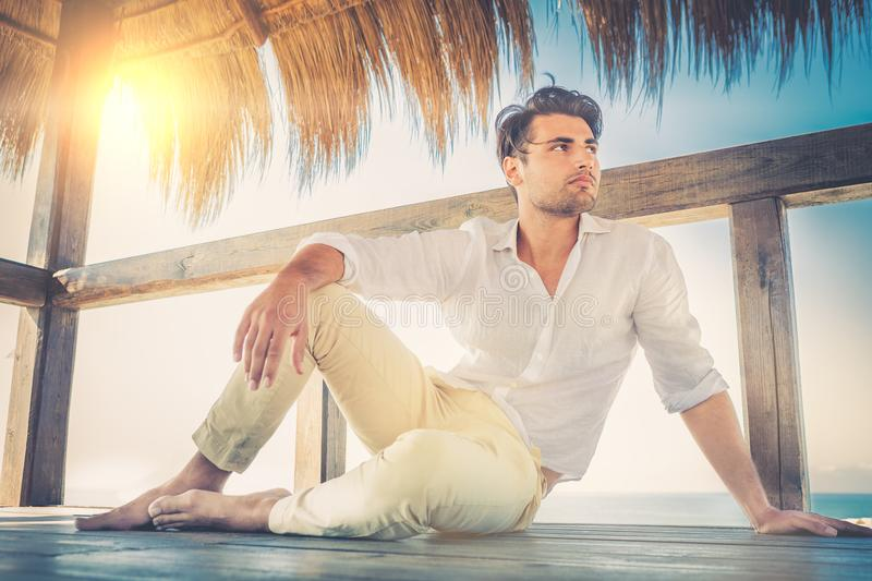 Beautiful young relaxed man in a small wooden deck. Strong summer warm light. S. Trendy haircut. White shirt and beige trousers royalty free stock images