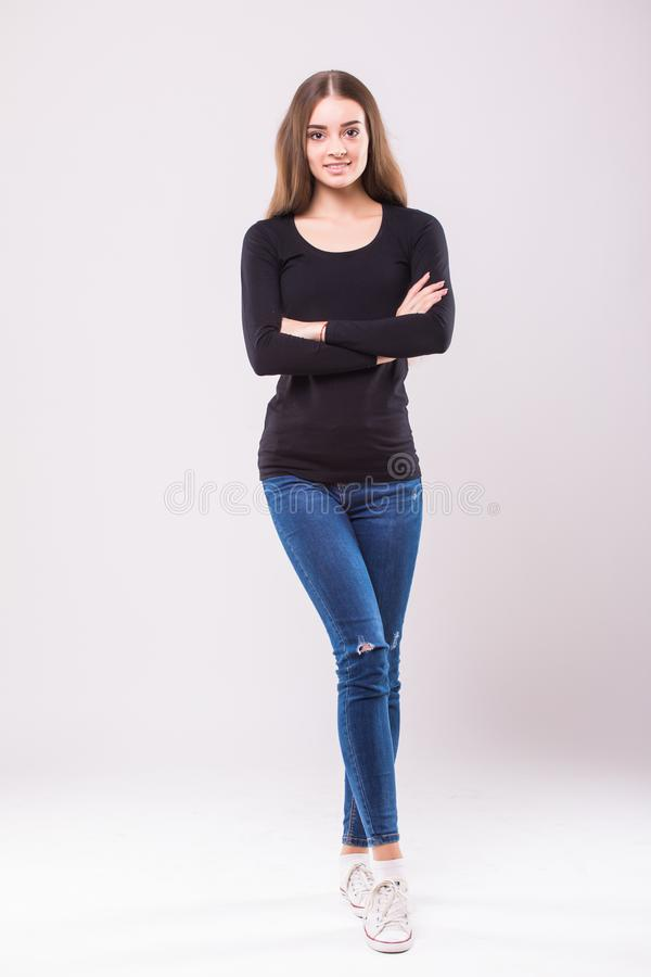 Beautiful young relaxed woman, full height, with crossed arms, isolated on white background royalty free stock images