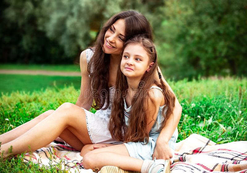 Beautiful young relaxing mother embracing her angry playful grimacing daughter on summer green grass background in sunny day stock photography