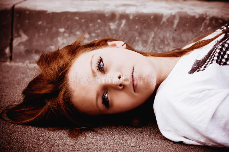 Beautiful young sad girl lying on asphalt