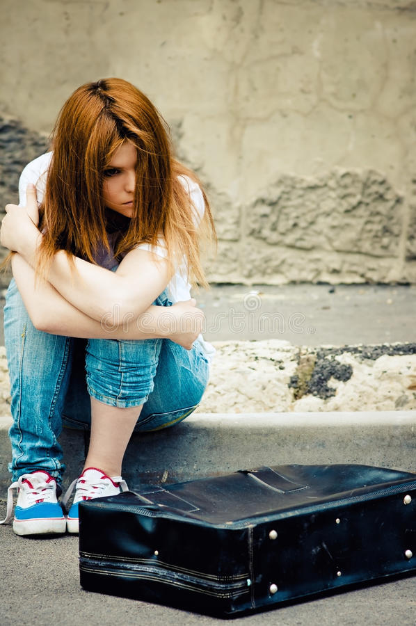 Beautiful young sad girl sitting on asphalt stock image