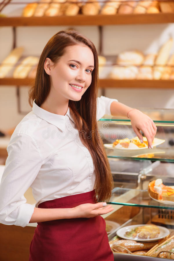 Beautiful young saleswoman in a bakery stock photography