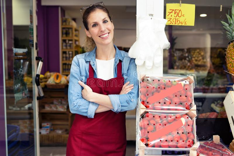 Beautiful young saleswoman looking at camera in health grocery shop. stock images