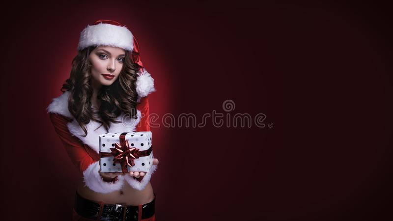 Beautiful young Santa girl with gift on red background. Copy space. royalty free stock photo