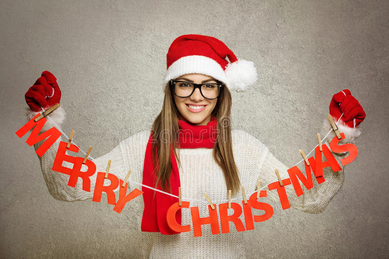 Beautiful young Santa girl with Merry Christmas text decoration. Beautiful young Caucasian happy young woman wearing Santa Claus costume with Merry Christmas stock photography