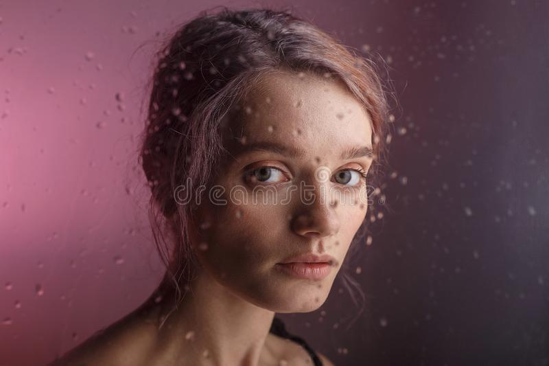 Pretty young girl looks into camera on purple background. blurry drops of water run down the glass in front of her face. Beautiful young sensual thoughtful royalty free stock images