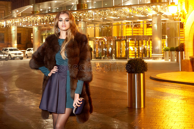 Beautiful young blonde wearing evening makeup in elegant fitting dress fashionable stylish expensive fur coat walk night stre royalty free stock images