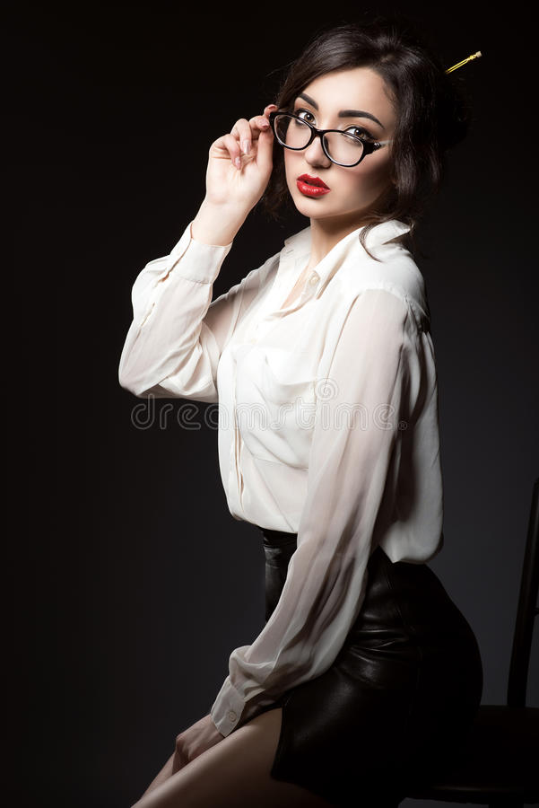 Beautiful young business woman with dark updo hair looking direct over her trendy glasses in modern frame. royalty free stock photo