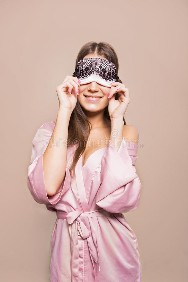 Beautiful young cute girl in bathrobe with sleeping mask on beige background royalty free stock photos