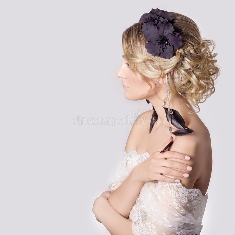 Beautiful young elegant sweet girl in the image of a bride with hair and flowers in her hair, delicate wedding makeup royalty free stock image