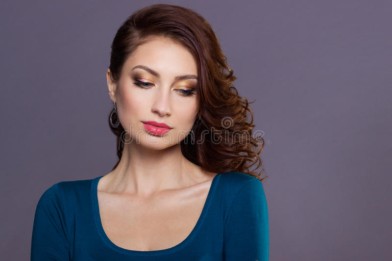 Beautiful young girl with curls with bright festive makeup, plump lips. the image to the new year, on Christmas evening stock photos