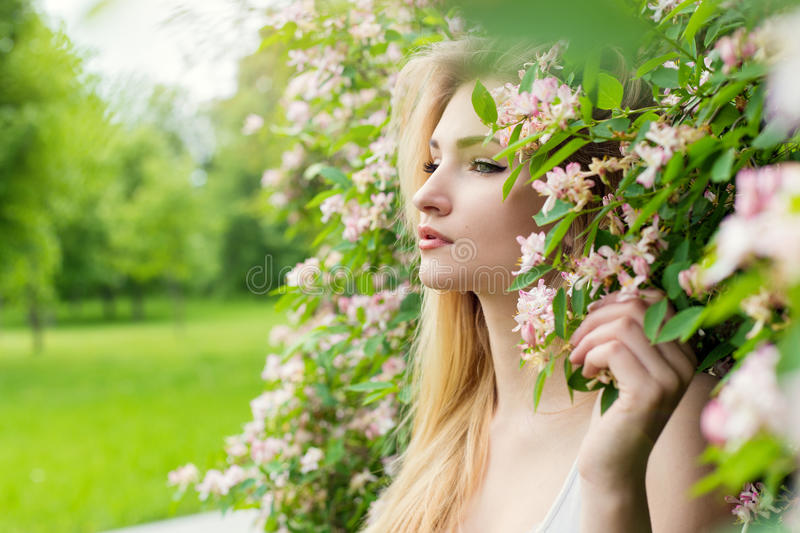 Beautiful young girl in flowers in the Park stock images