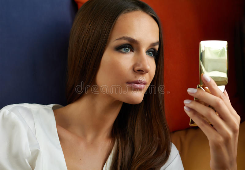 Beautiful young girl with long straight hair and evening make-up, dark painted eyes and pink lipstick looks in gold powder royalty free stock photography