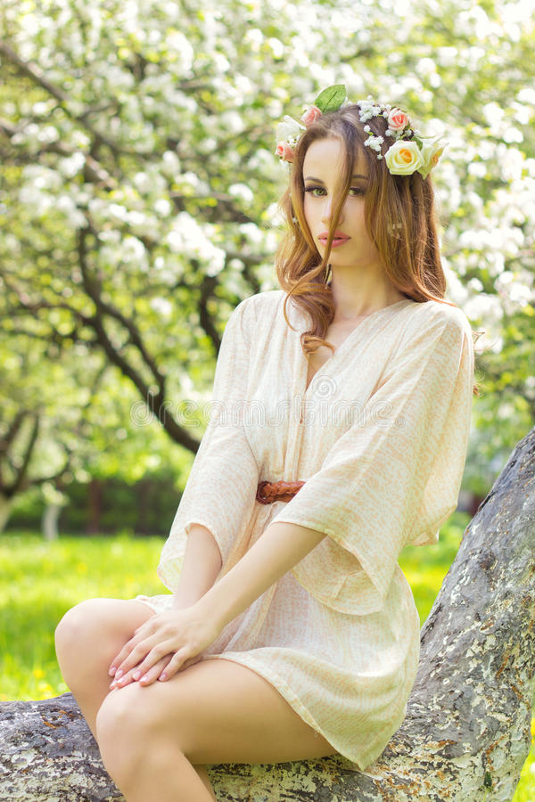 Beautiful young girl with red hair beautiful make up with flowers in her hair, sitting in a tree in a lush Apple orchard stock image