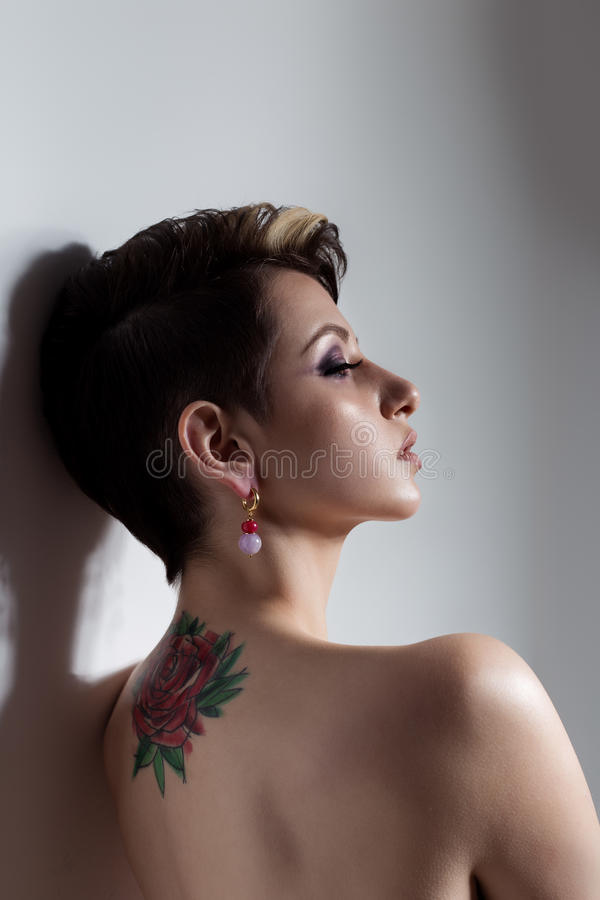 Beautiful young girl with short hair with tattoo on his back is against the wall with bare shoulders sad stock photos