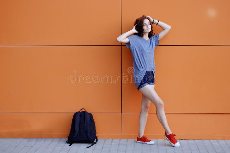 Beautiful young hipster girl standing near urban orange wall in blue shirt, denim shorts, sneakers with her pink royalty free stock images