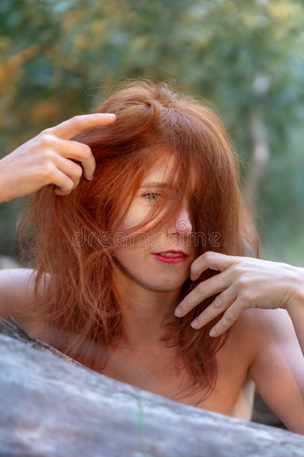 Beautiful young red-haired woman enjoys smiling happily playing at her beautiful glorious red hair royalty free stock photography