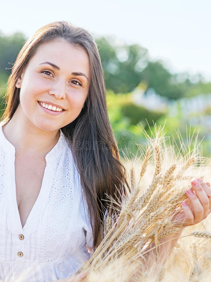 Beautiful young woman in golden wheat field at summer sunny day. Portrait of pretty smiling girl outdoor stock images