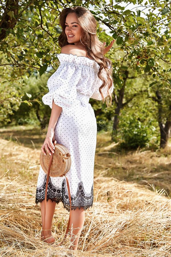 Beautiful young woman long hair bright makeup nature backgr. Ound landscape dry spike grass and apple trees garden summer model dressed in light white cotton stock images