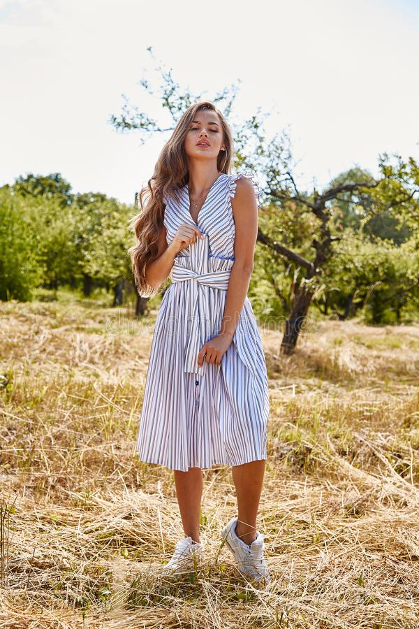 Beautiful young woman long hair bright makeup nature backgr. Ound landscape dry spike grass and apple trees garden summer model wear in light white cotton dress royalty free stock images