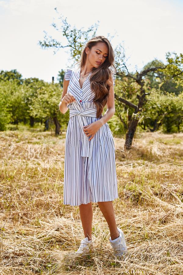 Beautiful young woman long hair bright makeup nature backgr. Ound landscape dry spike grass and apple trees garden summer model wear in light white cotton dress stock photos