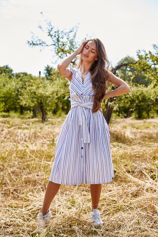 Beautiful young woman long hair bright makeup nature backgr. Ound landscape dry spike grass and apple trees garden summer model wear in light white cotton dress royalty free stock photos