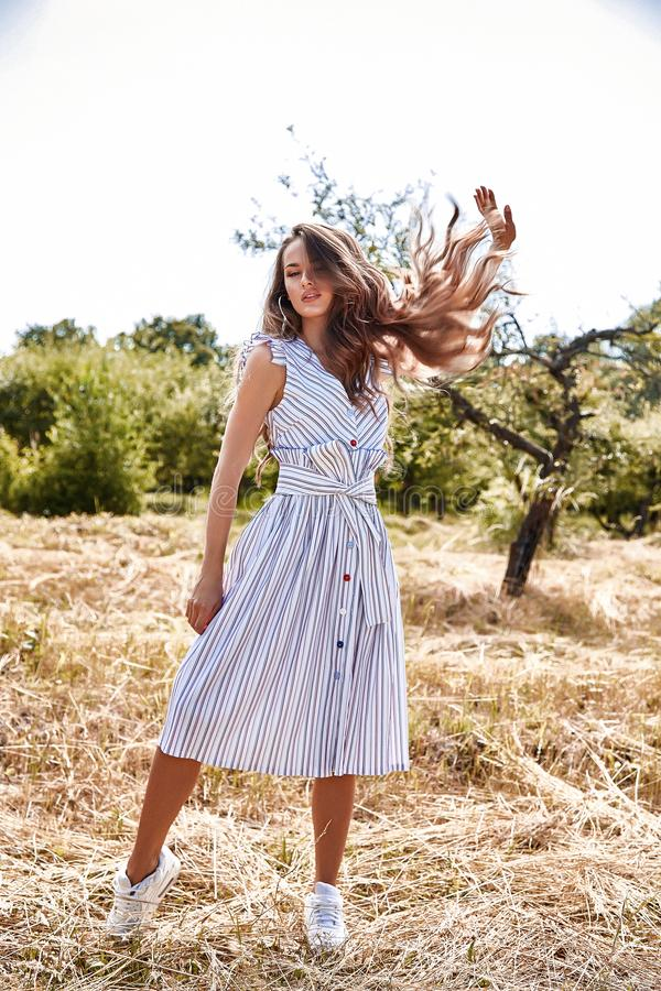 Beautiful young woman long hair bright makeup nature backgr. Ound landscape dry spike grass and trees garden summer model dressed in light white cotton dress royalty free stock photos