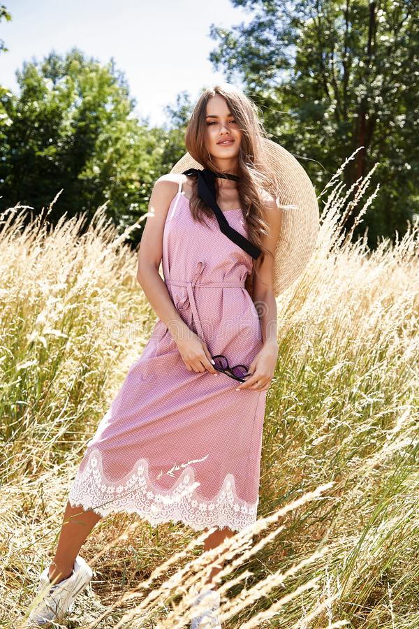Beautiful young woman long hair bright makeup nature backgr. Ound landscape dry spike grass and trees garden summer model dressed in cotton dress accessory straw stock photos