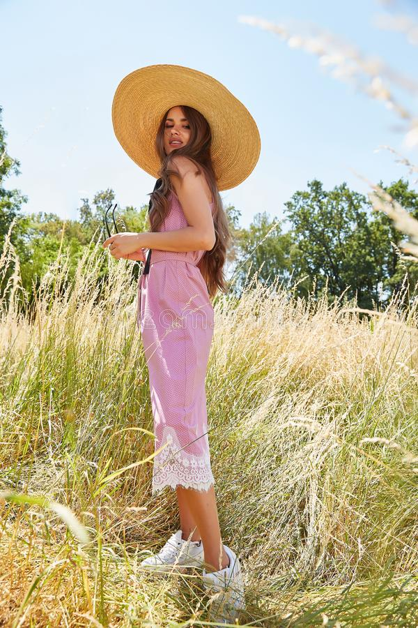 Beautiful young woman long hair bright makeup nature backgr. Ound landscape dry spike grass and trees garden summer model dressed in cotton dress accessory straw stock images