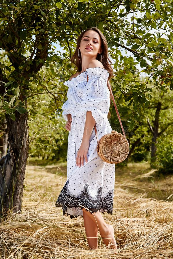 Beautiful young woman long hair bright makeup nature backgr. Ound landscape dry spike grass and apple trees garden summer model dressed in light white cotton royalty free stock photo