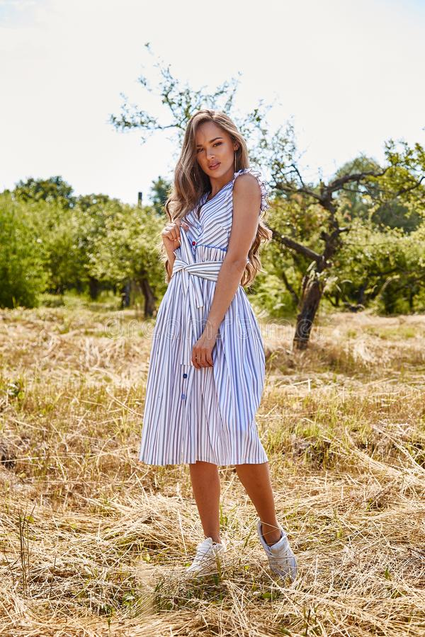 Beautiful young woman long hair bright makeup nature backgr. Ound landscape dry spike grass and apple trees garden summer model wear in light white cotton dress royalty free stock photography